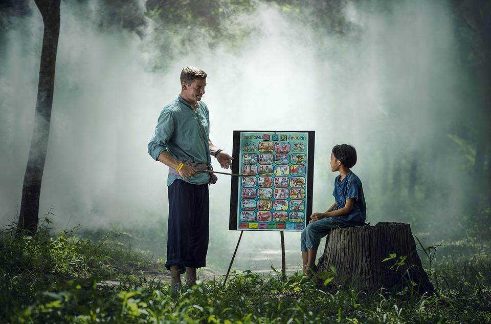 man teaching boy in jungle
